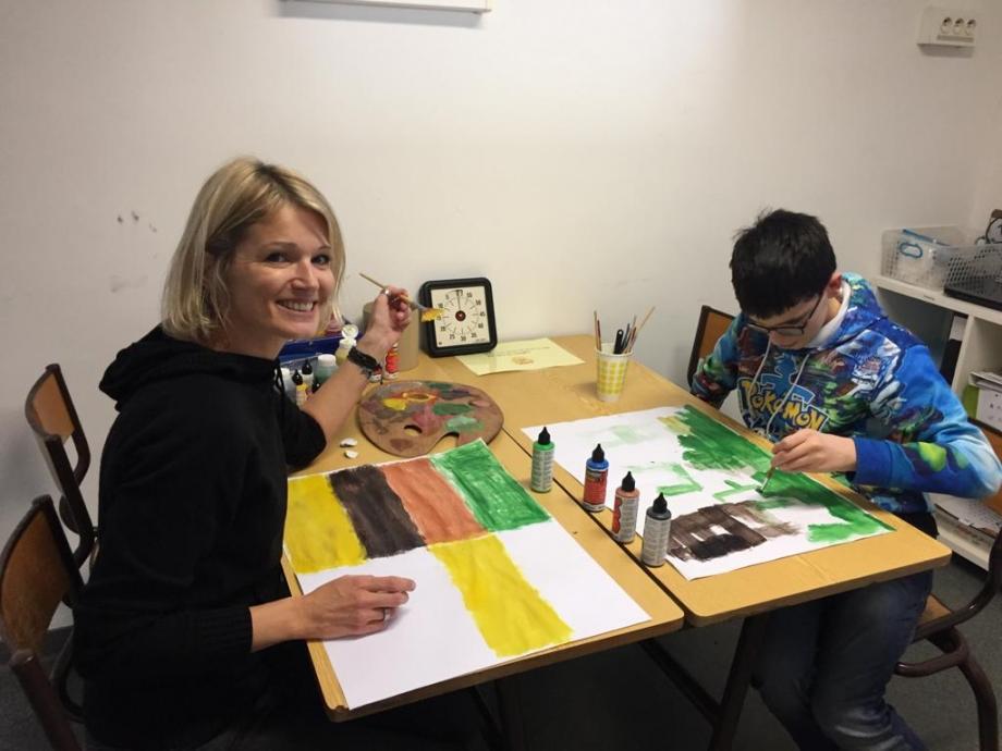 enfant entrain de peindre en atelier avec une bénévole